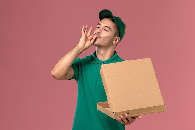 Курьер-мужчина в зеленой форме, вид спереди, держит коробку с едой и открывает ее на светло-розовом столе