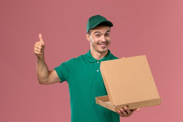 フードボックスを保持し、ピンクの机の上でそれを開く緑の制服を着た正面図の男性宅配便