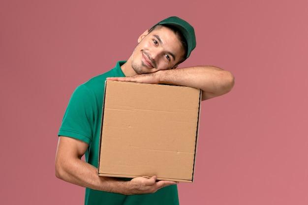 フードボックスを保持し、ピンクの背景に笑みを浮かべて緑の制服を着た男性宅配便の正面図