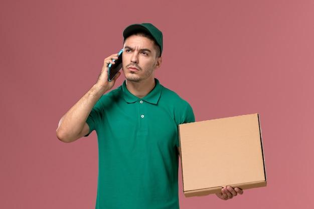 Курьер-мужчина, вид спереди в зеленой форме, держит коробку с едой и разговаривает по телефону на розовом столе