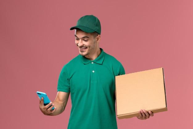 Курьер-мужчина, вид спереди в зеленой форме, держит коробку с едой и использует свой телефон на розовом фоне