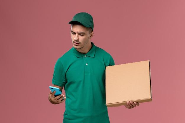 フードボックスを保持し、ピンクの背景に電話を使用して緑の制服を着た男性の宅配便の正面図