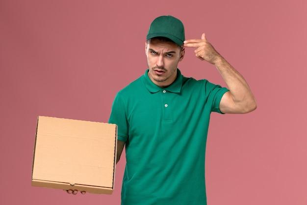 ピンクの背景にフードボックスを保持している緑の制服の正面図男性宅配便
