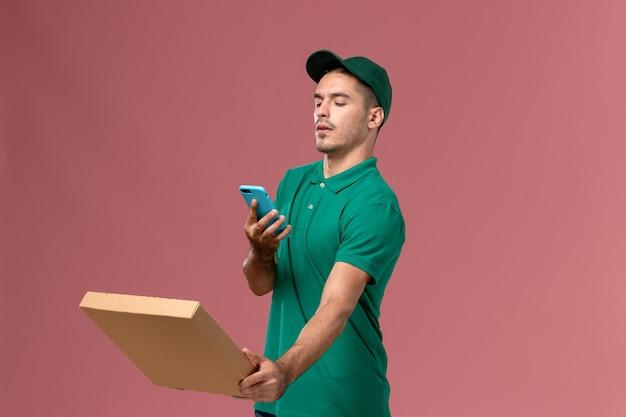 Курьер-мужчина, вид спереди в зеленой форме, держит коробку с едой и фотографирует ее на розовом фоне