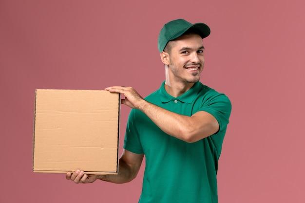 Курьер-мужчина в зеленой форме с улыбкой держит коробку для еды на розовом столе
