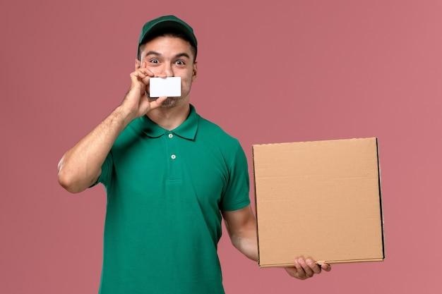 Курьер-мужчина, вид спереди в зеленой форме, держит коробку для еды с белой карточкой на светло-розовом фоне