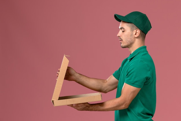 Вид спереди мужской курьер в зеленой форме, держащий коробку для доставки еды на розовом фоне