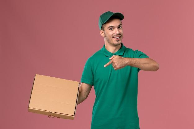 Курьер-мужчина в зеленой форме, держа коробку для доставки еды на розовом полу, вид спереди