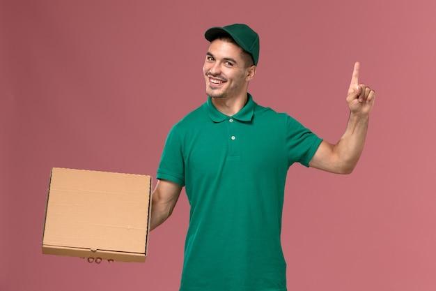 Курьер-мужчина в зеленой форме, держа коробку для доставки еды с поднятым пальцем на розовом фоне, вид спереди