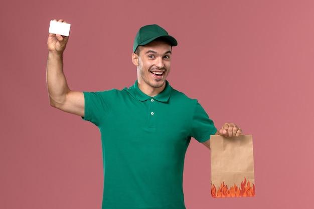 Курьер-мужчина, вид спереди в зеленой форме, держит пакет с едой и карточку на розовом фоне