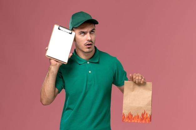 淡いピンクの背景で考える食品パッケージとメモ帳を保持している緑の制服を着た正面図男性宅配便
