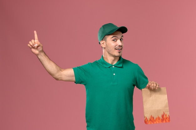 Курьер-мужчина, вид спереди в зеленой форме, держит пакет с едой и поднимает палец на светло-розовом фоне
