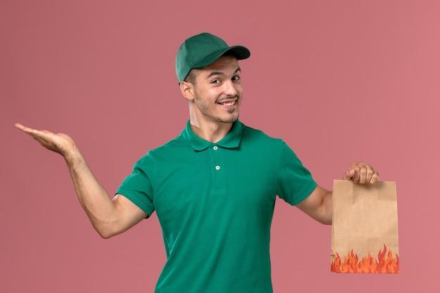 Курьер-мужчина, вид спереди в зеленой форме, держит пакет с едой и улыбается на светло-розовом фоне