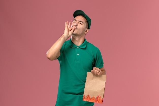 Курьер-мужчина в зеленой форме, держа пакет с едой на светло-розовом фоне, вид спереди