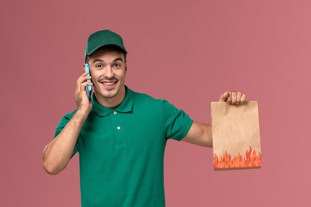 Курьер-мужчина, вид спереди в зеленой форме, держит пакет с едой во время разговора по телефону на розовом