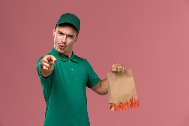 ピンクの背景に紙の食品パッケージを保持している緑の制服の正面図男性宅配便