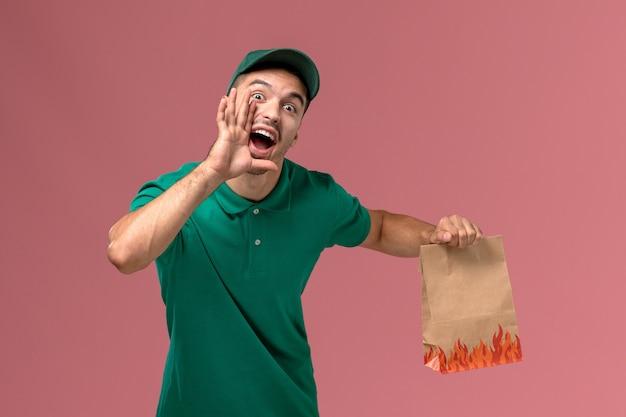 淡いピンクの背景で叫んでいる紙の食品パッケージを保持している緑の制服の正面図男性宅配