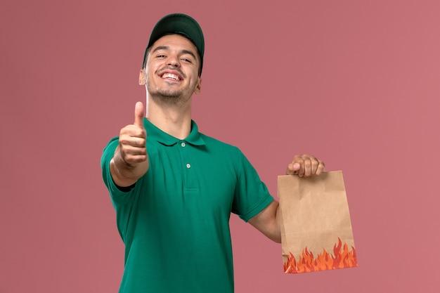 Курьер-мужчина в зеленой форме, держащий бумажный пакет с продуктами, улыбается на светло-розовом фоне, вид спереди