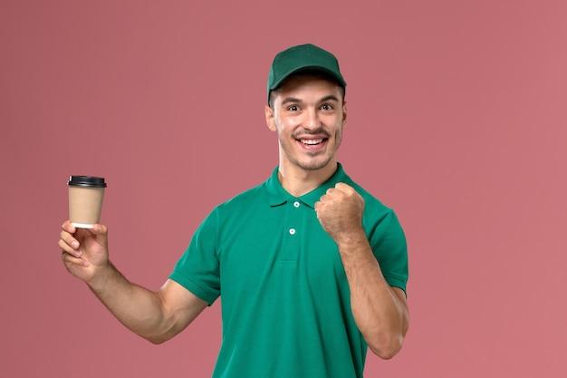 ピンクの背景にコーヒーカップを喜んで保持している緑の制服を着た正面図男性宅配便