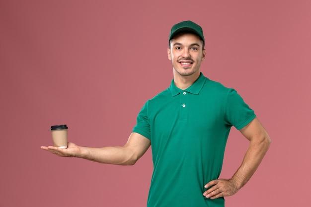 ピンクの背景に笑顔とコーヒーカップを保持している緑の制服を着た正面図男性宅配便