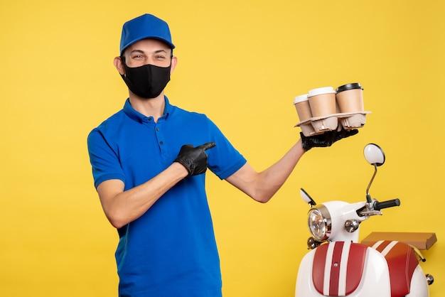 노란색 작업 유니폼 covid- 배달 작업 서비스에 커피를 들고 마스크에 전면보기 남성 택배