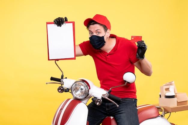 Курьер-мужчина, вид спереди в маске, держит примечание к файлу и банковскую карту на желтом