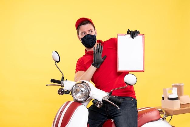 黄色のファイル ノートを保持しているマスクの男性宅配便の正面図