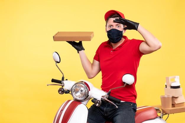 Вид спереди мужской курьер в маске, держащий коробку с едой на желтом