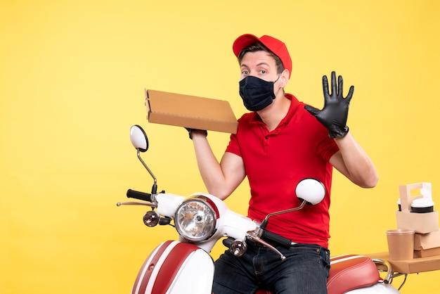 黄色のフード ボックスを保持しているマスクの正面男性宅配便