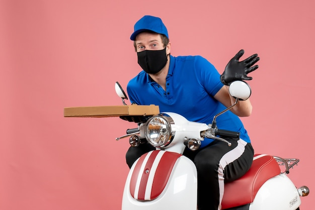 ピンクのピザの箱を保持しているマスクの正面男性宅配便