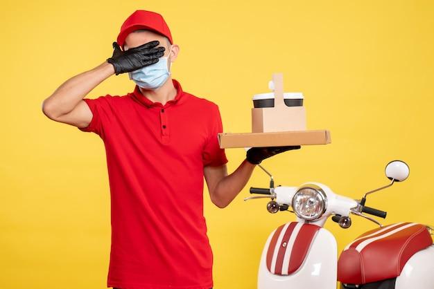 Вид спереди мужчина-курьер в маске с доставкой кофе и коробкой, закрывающей глаза на желтом цвете, служба covid- virus, рабочая униформа, пандемия.