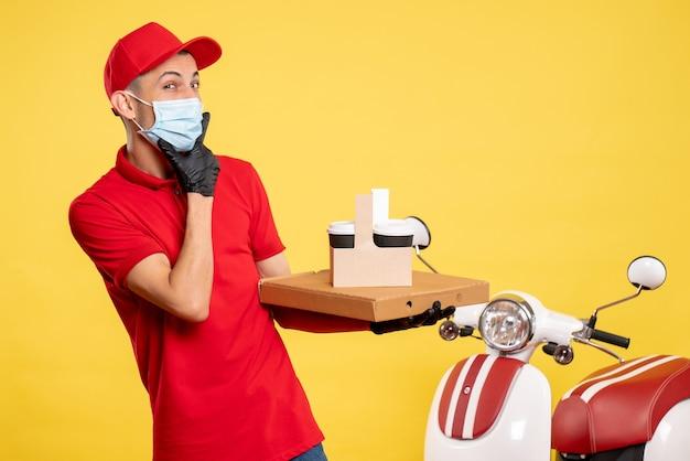 노란색 서비스 covid 유행성 컬러 바이러스 작업 유니폼에 배달 커피와 상자가있는 마스크의 전면보기 남성 택배