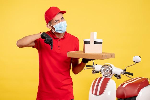 Вид спереди мужчина-курьер в маске с доставкой кофе и коробкой на желтых цветах служба covid- virus работа униформа пандемическая работа