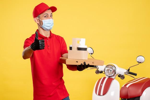 Курьер-мужчина, вид спереди в маске с доставкой кофе и коробкой на желтом служебном вирусе пандемического цвета