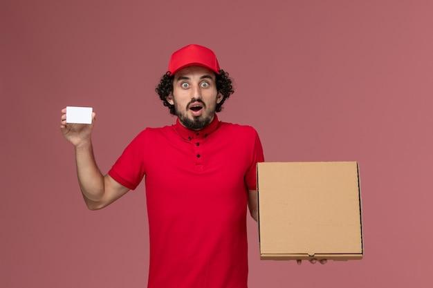 빨간 셔츠와 케이프 핑크 벽에 배달 음식 상자와 카드를 들고 전면보기 남성 택배