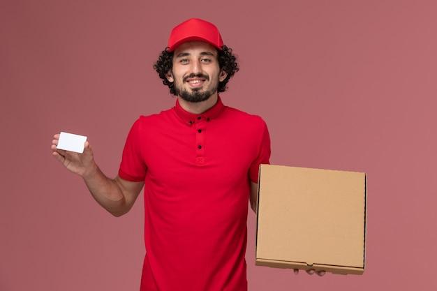 ピンクの壁に配達フードボックスとカードを保持している赤いシャツとケープの正面図男性宅配便