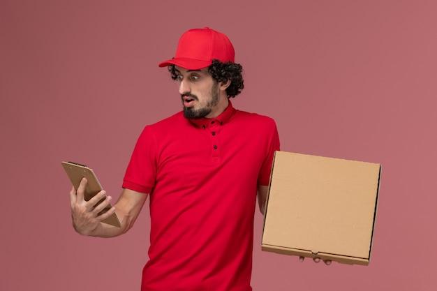 ピンクの壁に配達フードボックスとメモ帳を保持している赤いシャツとケープの正面図男性宅配便