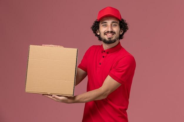 Курьер-мужчина в красной рубашке и плаще, вид спереди, держит коробку с доставкой на светло-розовой стене