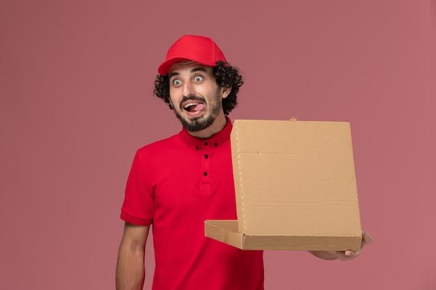 淡いピンクの壁に配達フードボックスを保持している赤いシャツと岬の正面図男性宅配便