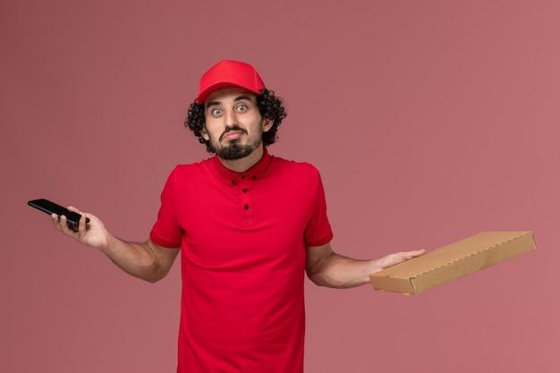 Курьер-мужчина, вид спереди в красной рубашке и плаще, держит пустую коробку для еды и смартфон на розовой стене