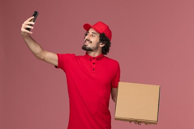 Курьер-мужчина в красной рубашке и плаще, держащий пустую коробку для доставки еды, фотографируется на розовой стене
