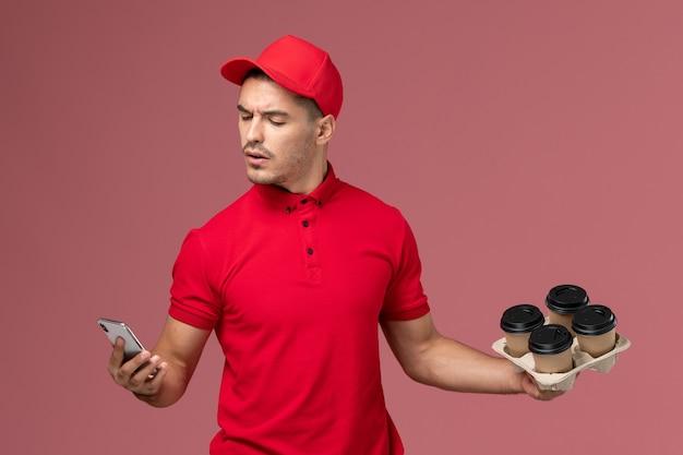 Курьер-мужчина, вид спереди в красной форме и накидке, держит кофейные чашки для доставки и использует свой телефон на розовой стене