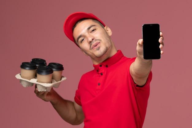 Курьер-мужчина, вид спереди в красной форме и плаще, держащий кофейные чашки с телефоном на светло-розовой стене