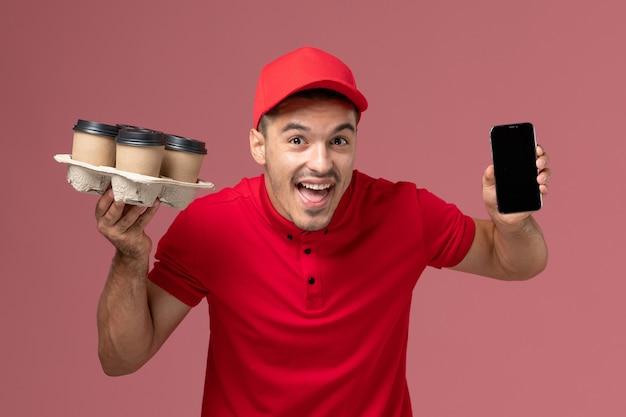 Курьер-мужчина, вид спереди в красной форме и плаще, держащий кофейные чашки с телефоном на розовой стене