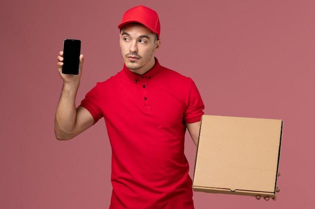 Курьер-мужчина, вид спереди в красной форме и плаще, держит коробку с едой вместе со своим телефоном на розовой стене.