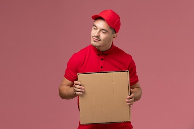 Курьер-мужчина в красной форме и плаще, держащий коробку с едой на розовой стене, вид спереди
