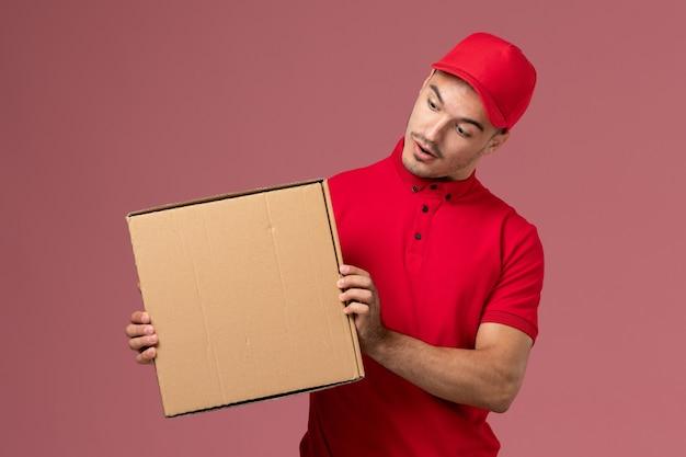 ピンクの壁の労働者の仕事でフードボックスを保持している赤い制服と岬の正面図男性宅配便