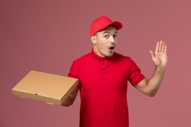 Курьер-мужчина, вид спереди в красной форме и плаще, держит коробку для доставки еды на розовой стене