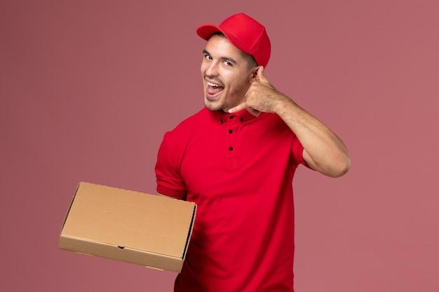 Курьер-мужчина в красной форме и плащ, держащий коробку для доставки еды, позирует на розовой стене