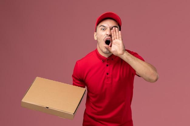 Вид спереди курьер-мужчина в красной форме и плаще, держащий коробку для доставки еды, кричит на розовой стене рабочего места